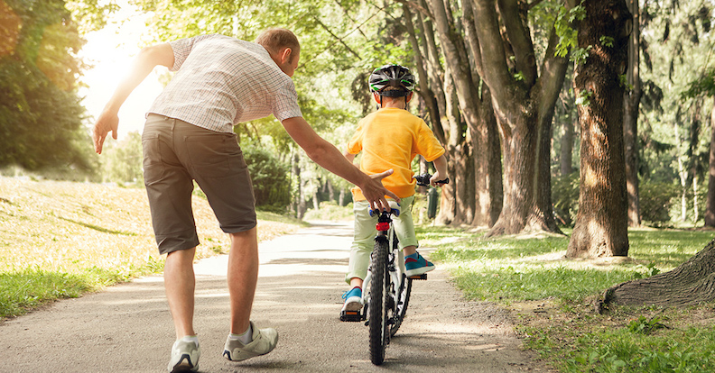 Dad Teaching A Son How To Ride A Bike